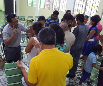 A pastor praying at a leader training session