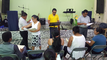 Four Bible teachers passing out graded exams in Coatepeque, Guatemala