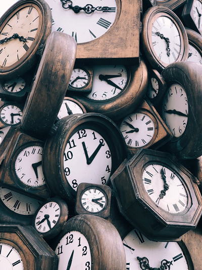 Photo of a variety of clocks, all set at different times; image courtesy of https://unsplash.com/@jontyson