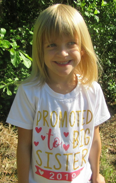 Image of a smiling girl wearing a t-shirt that says, 'Promoted to Big Sister 2019