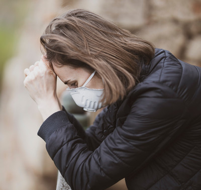 Image of a woman praying while wearing a surgical mask