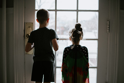 Photo of a small boy and girl looking through the window.