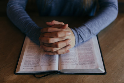 Image of praying hands resting on an open Bible
