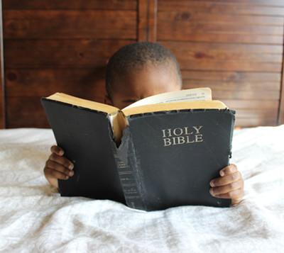 Image of boy reading a worn Bible