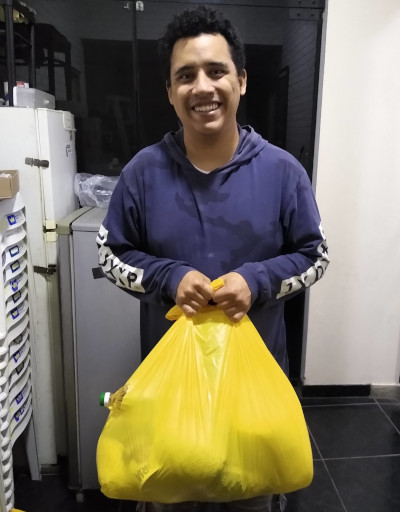 A young Christian brother holding a yellow 'blessing bag'
