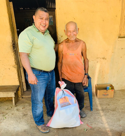 Pastor sharing a sack of groceries with an old man in town.