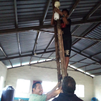 Installing lighting on a makeshift ladder in Guatemala