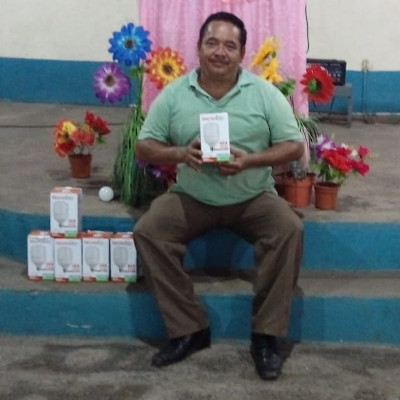 A Guatemalan pastor with a stack of institutional-grade light bulbs for his sanctuary