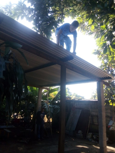Man affixing zinc roofing sheets to an open-air sanctuary in Guatemala