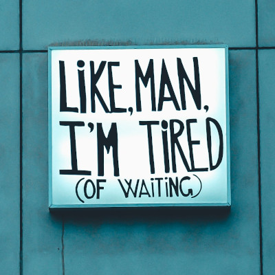 Photo of a sign which says, 'Like man, I'm tired (of waiting).'